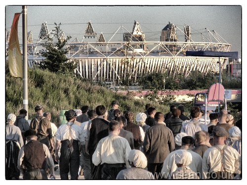 working men and women walking towards the Olympic Stadium for the opening ceremony rehearsal