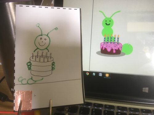 My interactive storybook, showing a caterpillar on the page with a cake and a similar picture on the screen in Scratch