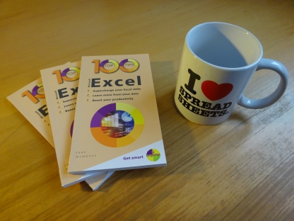 Photo of 100 Top Tips: Microsoft Excel, with a mug that says I heart spreadsheets on it