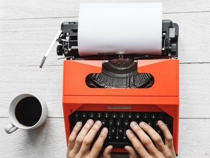 Photo of an orange typewriter on a desk, with a nice cup of tea