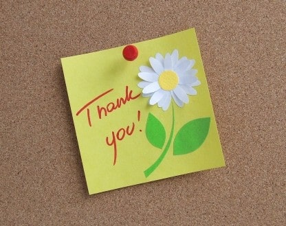 Thank you on a sticky note on a pinboard