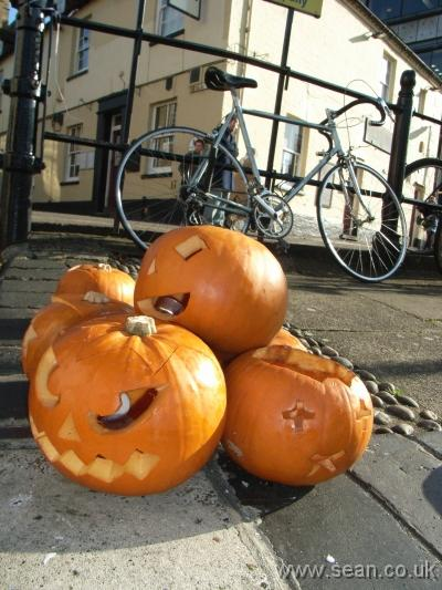 a pile of carved pumpkins with a bicycle